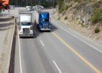 two trucks driving uphill, Fraser River; BC; Canada.