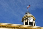 Upwards view of clock tower with Canada's flag on top of it